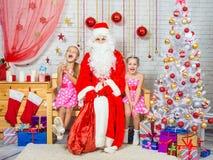 愉快的女孩和圣诞老人坐在圣诞节设置的一条长凳 免版税库存图片