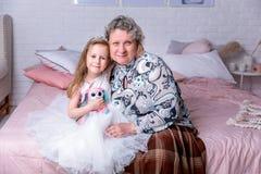 愉快的女孩和她的祖母一起坐并且在卧室拥抱 他们smilling并且亲吻 ?? 库存照片