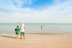 愉快的女孩和家庭在海滩 免版税图库摄影