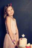 愉快的女孩和杯形蛋糕在生日 库存图片