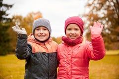 愉快的女孩和男孩挥动的手在秋天公园 免版税库存照片