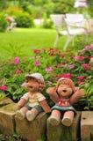 愉快的女孩和男孩玩偶在庭院里 免版税图库摄影