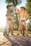 愉快的女孩和男孩骑马在公园骑自行车 库存照片