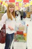 愉快的女孩和购物车用食物 图库摄影