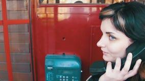 愉快的女孩在一个红色电话亭谈话在街道的电话 股票录像