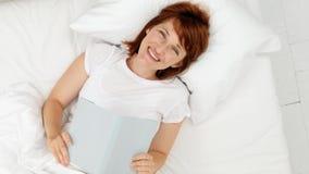 愉快的女孩在一张白色床上的读一本书 顶视图 股票录像