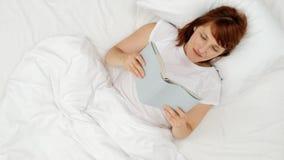 愉快的女孩在一张白色床上的读一本书 顶视图 影视素材