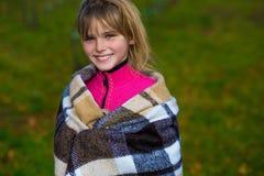 愉快的女孩在一条温暖的毯子的公园 免版税库存图片