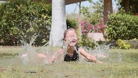 愉快的女孩在公园喜欢飞溅放置在水坑在草坪 股票视频