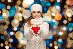 愉快的女孩在冬天穿衣与红色心脏 图库摄影