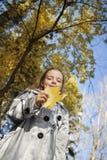愉快的女孩在叶子秋天 免版税库存照片