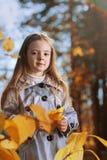 愉快的女孩在叶子秋天 库存图片