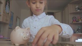 愉快的女孩在存钱罐中存金钱在她的家 插入硬币的孩子入存钱罐,室内财政概念 孩子 股票录像