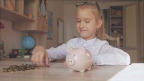 愉快的女孩在存钱罐中存金钱在她的家 插入硬币的孩子入存钱罐,室内财政概念 孩子 股票视频