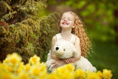 愉快的女孩在开花的庭院里 免版税库存照片