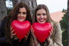 愉快的女孩在手上的拿着红色心脏 库存照片