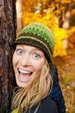 愉快的女孩在拥抱树的Autum森林里 免版税库存图片