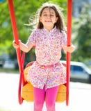 年轻愉快的女孩在操场摇摆 免版税库存图片