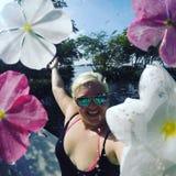 愉快的女孩在有花和太阳镜的天堂 免版税库存图片