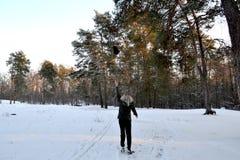愉快的女孩在森林投掷一个帽子  免版税库存图片