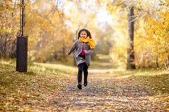 愉快的女孩在秋天公园跑 免版税图库摄影