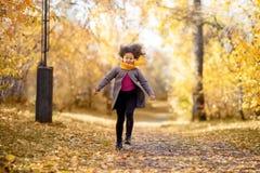 愉快的女孩在秋天公园跑 库存图片