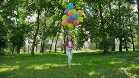 愉快的女孩在绿色晴朗的公园走并且拿着五颜六色的气球 影视素材