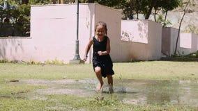 愉快的女孩在绿色草坪的水坑跑慢动作的 股票视频
