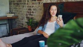 愉快的女孩在网上聊天使用看电话照相机的智能手机,谈话在微笑的坐床在卧室  股票录像