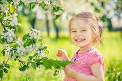 愉快的女孩在苹果树庭院里 免版税库存照片