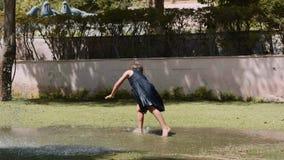 愉快的女孩在草坪的水坑跳并且做杂技轮子 股票视频