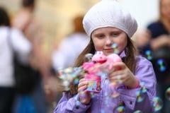 愉快的女孩在街道上使用与肥皂泡开枪 免版税库存照片