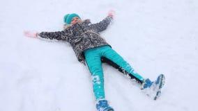 愉快的女孩在雪说谎并且描述天使在降雪期间在冬天 股票录像