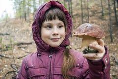 愉快的女孩在他的手上的拿着白色蘑菇 免版税库存图片