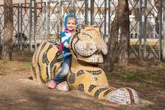 愉快的女孩坐一只老虎的雕塑在操场的在阿纳帕 图库摄影