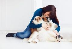 愉快的女孩坐与白种人牧羊人小狗的地板 图库摄影