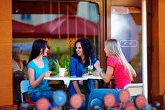 愉快的女孩坐咖啡馆大阳台,户外 免版税图库摄影