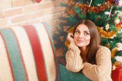 愉快的女孩坐在圣诞树和梦想下 免版税库存图片