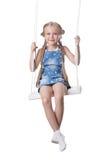 愉快的女孩坐摇摆 免版税库存图片