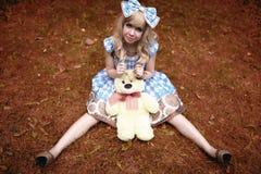 愉快的女孩坐有作为玩偶夏令时穿戴的玩具熊的草甸 免版税图库摄影