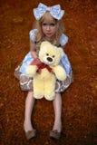 愉快的女孩坐有作为玩偶夏令时穿戴的玩具熊的草甸 免版税库存照片
