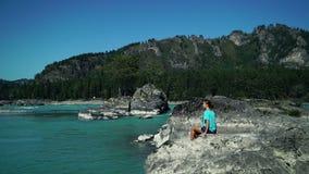 愉快的女孩坐石头由山的一条快速的河 股票录像