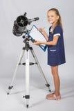 愉快的女孩天文学家看起来愉快在站立在望远镜旁边的图片 库存照片