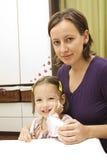 愉快的女孩她的母亲 免版税库存照片