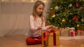愉快的女孩开头圣诞节礼物在家 股票视频