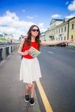 年轻愉快的女孩抓住有城市地图的一辆出租汽车在手上 站立在街道微笑的一名美丽的愉快的妇女的画象 免版税库存图片