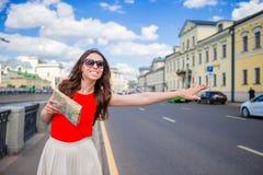 年轻愉快的女孩抓住有城市地图的一辆出租汽车在手上 站立在街道微笑的一名美丽的愉快的妇女的画象 库存图片