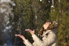 愉快的女孩投掷的雪在冬天holdays的天空中 免版税库存图片