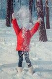 愉快的女孩投掷的雪在天空中在晴天 库存照片