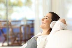愉快的女孩放松的听到在沙发的音乐 库存照片